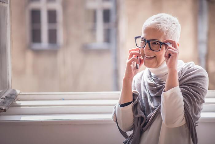 Older woman wearing glasses, talking on phone