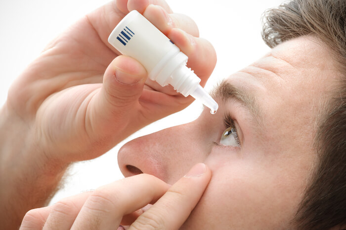Man putting drops in his eyes