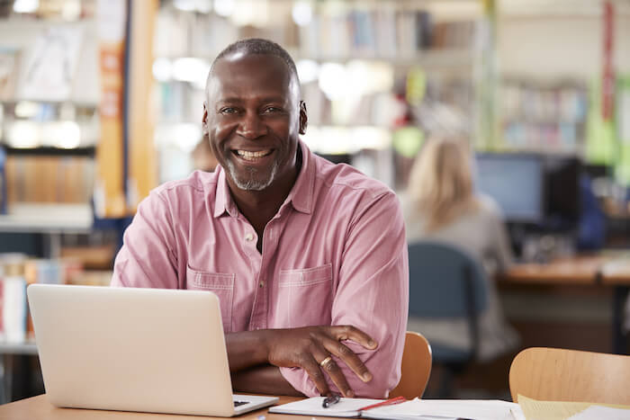 Middle-aged man smiling in front of laptop